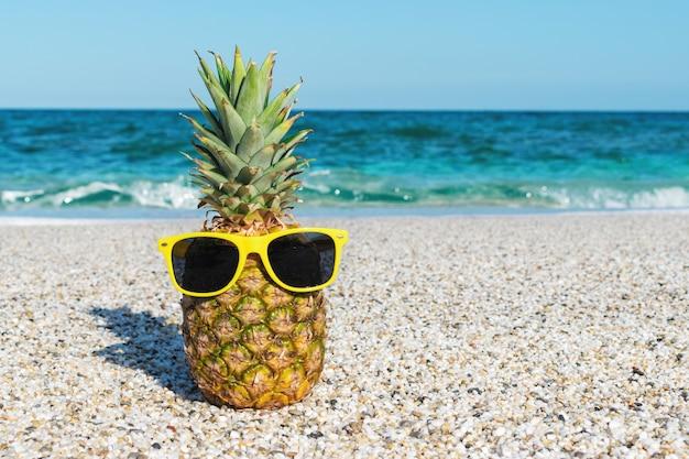 Abacaxi hipster de óculos escuros na praia