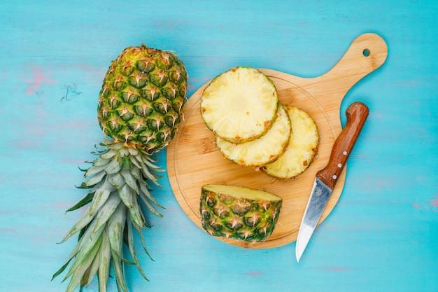 Abacaxi inteiro e fatiado com uma faca de fruta em uma placa de corte em azul ciano, plano leigos.