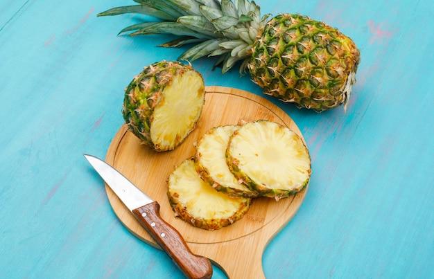 Abacaxi inteiro e fatiado com uma faca em uma placa de corte em azul ciano, vista de alto ângulo.