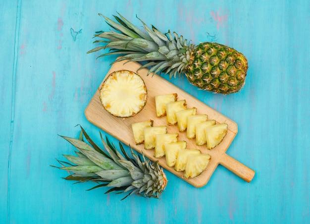 Abacaxi inteiro e fatiado em uma vista superior da placa de corte em um ciano azul