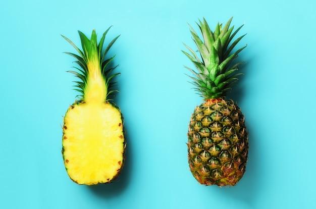 Abacaxi inteiro e meia fruta fatiada em azul