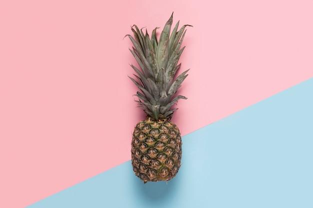 Abacaxi inteiro em um fundo rosa e azul