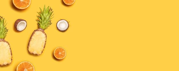 Abacaxi, limões, laranjas e cocos em um fundo amarelo.