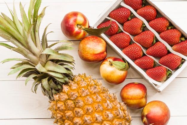 Abacaxi; maçãs e morangos no pano de fundo de madeira