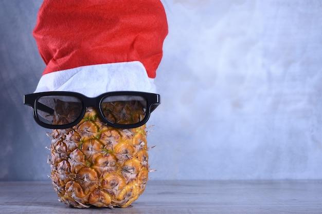 Abacaxi maduro, ananás com óculos de sol no chapéu de papai noel. ano novo conceito de fruta