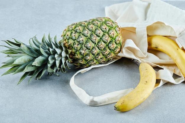 Abacaxi maduro e banana em um saco branco na mesa azul.