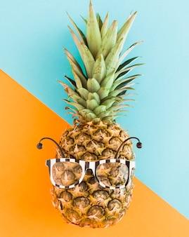 Abacaxi na moda em óculos de sol em plano de fundo multicolorido
