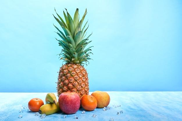 Abacaxi rodeado de frutas em fundo azul com espaço de cópia