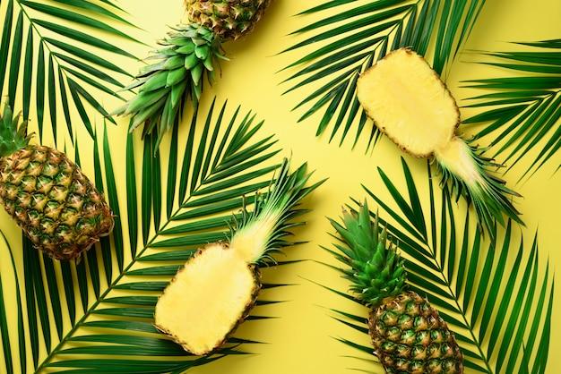 Abacaxis e folhas de palmeira tropicais no fundo amarelo pastel. conceito de verão.