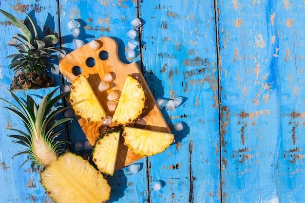 Abacaxis frescos e cubos de gelo em um fundo azul de madeira