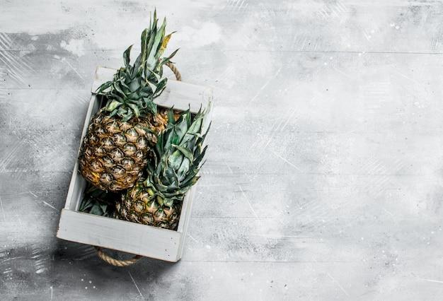 Abacaxis maduros e suculentos na caixa. em fundo rústico
