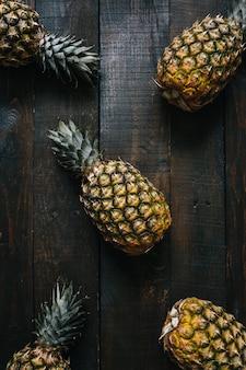 Abacaxis maduros no fundo escuro de madeira. conceito criativo de frutas tropicais.