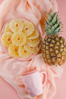 Abacaxis secos em um prato com abacaxi fresco e copo na superfície rosa e têxtil
