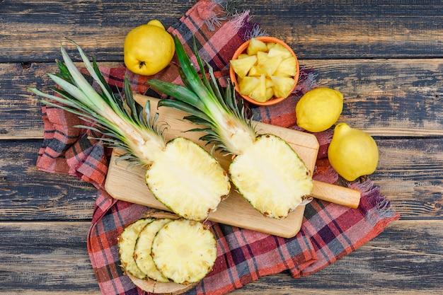 Abacaxis suculentos cortados com dois marmelos e um limão no placas de madeira e bacia na superfície de madeira velha do grunge e pano de piquenique, configuração lisa.