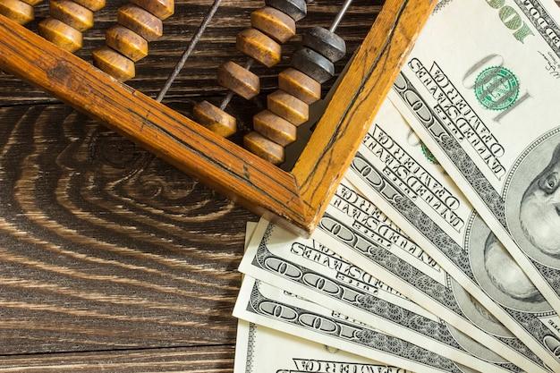 Ábaco de madeira velho e algumas notas de dólar sobre uma mesa de madeira