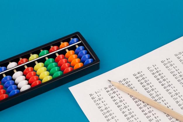 Ábaco para aritmética mental, sobre um fundo azul, com exemplos para resolver.