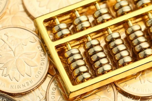 Abacus dourado com moedas de ouro chinesas de rmb como fundo