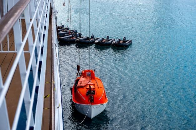 Abaixando o barco salva-vidas laranja para regar nas águas do ártico, svalbard. abandone a broca do navio. treinamento de barco salva-vidas. homem a bordo de broca.