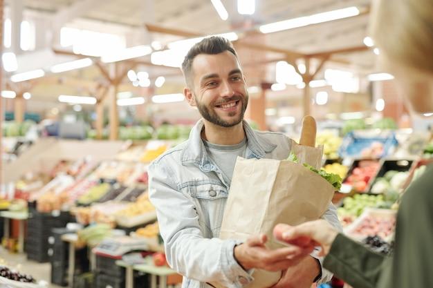 Abaixo, a imagem de uma mulher irreconhecível dando pêssego suculento ao marido enquanto eles compram frutas no mercado