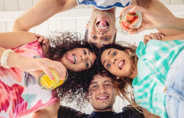 Abaixo a vista de jovens felizes com as cabeças juntas e segurando bebidas saudáveis, se divertindo em uma festa de verão. conceito de estilo de vida dos jovens.