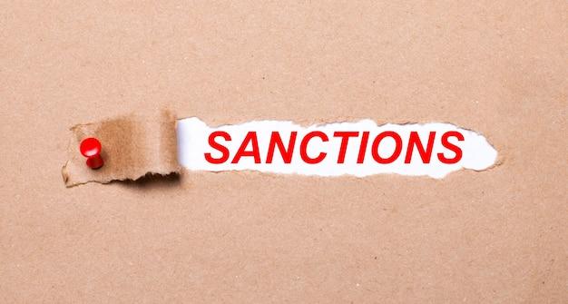Abaixo da tira rasgada de papel kraft presa com um botão vermelho está um papel branco sanções