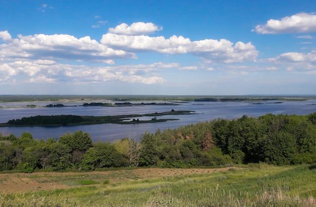 Abaixo, sob a colina, há um grande rio contra o fundo de nuvens claras e um céu azul