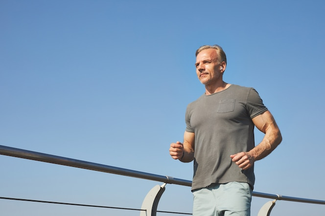 Abaixo, visualização do conteúdo homem maduro ativo em camiseta cinza, dobrando os braços e correndo ao ar livre