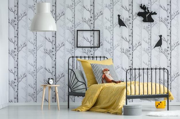 Abajur acima do banquinho com relógio no quarto infantil branco com o brinquedo da raposa vermelha na cama com travesseiro estampado