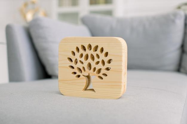 Abajur de madeira com imagem de árvore, no interior elegante da sala de estar em casa leve, no sofá moderno cinza. decoração e acessórios para casa.