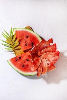 Abastecimento de inverno: fatias de melancia seca com pedaços frescos em fundo branco.