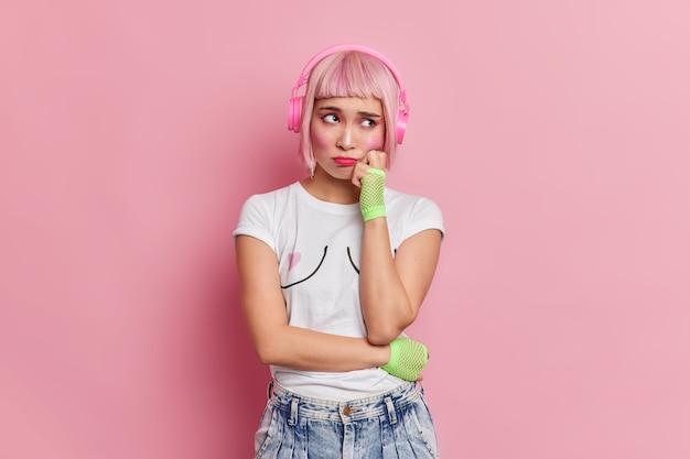 Abatida descontente mulher asiática com expressão infeliz mantém a mão na bochecha veste camiseta casual jeans ouve música através de fones de ouvido sem fio chateada por ter um dia de azar