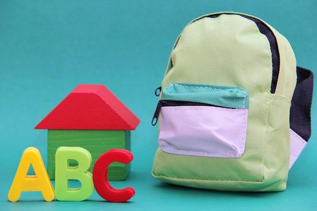 Abc - letras do alfabeto inglês à vontade de uma casa de madeira e uma mochila em um fundo verde.