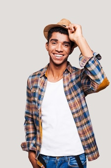 Aberto e sociável. hipster afro-americano jovem e bonito segurando o chapéu