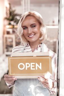 Abertura de um café. mulher loira atraente e encantada sorrindo para você enquanto está atrás da porta de vidro