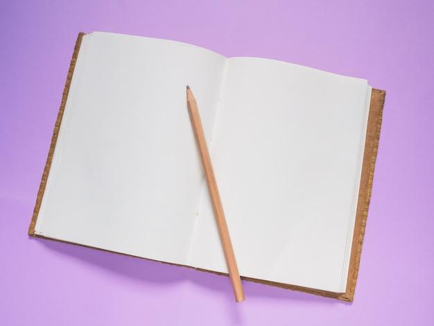 Abertura do caderno escolar sobre um fundo roxo