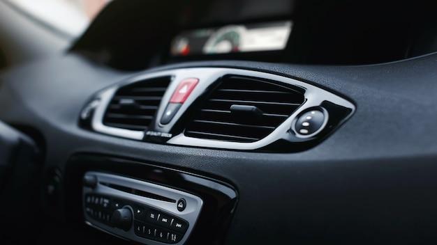 Aberturas de ventilação com defletores de fluxo de ar e botão de luzes de emergência do carro entre eles