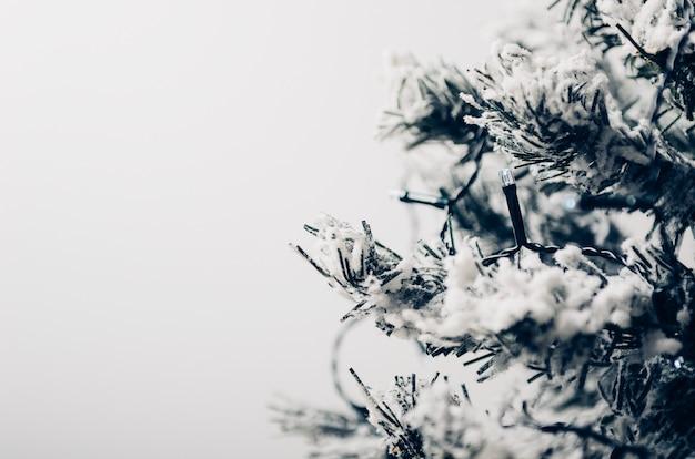 Abeto artificial com neve com uma festão elétrica.