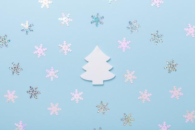 Abeto branco de composição de natal e flocos de neve em fundo azul pastel