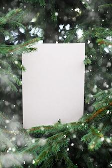 Abeto com cartão de papel vazio de ofício nos galhos. efeito de neve.