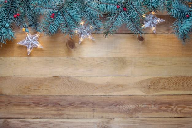 Abeto de natal e festão no fundo de madeira.
