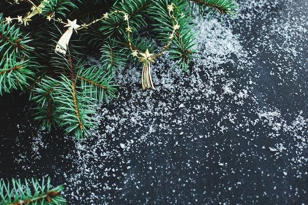 Abeto de natal na superfície escura com neve