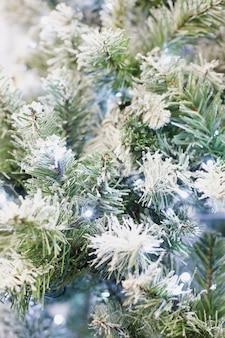 Abeto verde artificial sob a neve com guirlanda