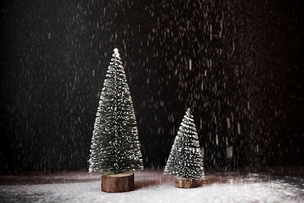 Abetos decorativos entre a queda de neve