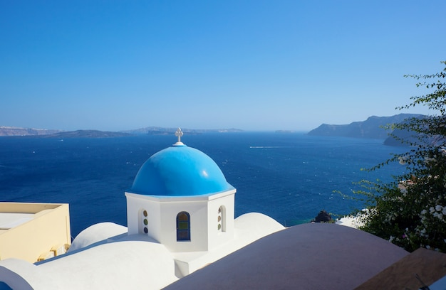Abóbada azul da igreja e da água do mar azul em santorini.