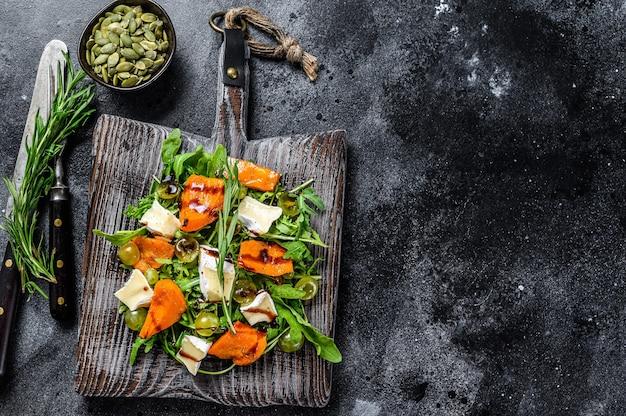 Abóbora assada com queijo camembert e ervas. conceito de comida vegana saudável. fundo preto. vista do topo. copie o espaço.