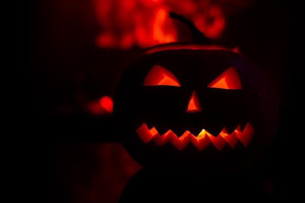 Abóbora assustadora para a celebração do halloween no fundo das chamas.