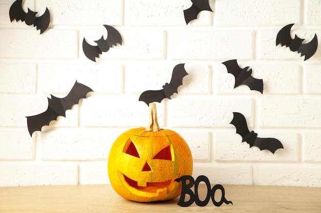 Abóbora brilhante esculpida e morcegos pretos sobre fundo claro. celebração de halloween. vista do topo