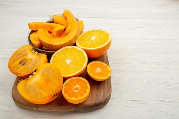 Abóbora butternut em tigelas corta caqui, mandarinas e laranjas na tábua de cortar no espaço livre da mesa branca