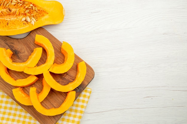 Abóbora butternut picada em uma tábua em um papel de cozinha xadrez branco e amarelo em uma mesa cinza. vista inferior