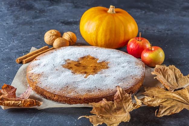Abóbora caseira americana ou torta de maçã com noz e folhas secas de outono na mesa rústica.